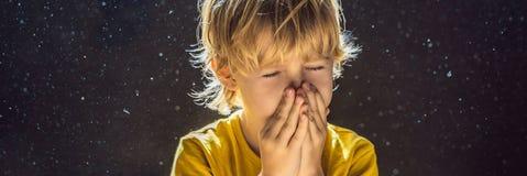 Allergie zum Staub Jungenniesen, weil er allergisch ist, Staubfliegen in der Luft abzuwischen, die durch helle FAHNE hintergrundb stockbilder