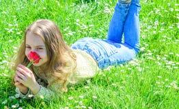Allergiekonzept Kind genießen Duft der Tulpe beim Lügen an der Wiese Mädchen mit dem langen Haar, das auf grassplot, Gras liegt stockfotografie