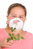 Allergies. Concept image of a girl with allergies featuring a young girl holding a rose in front of her face while she wears a dust mask Royalty Free Stock Image