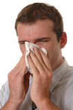 Allergies. A young man with allergies sneezing into a tissue Royalty Free Stock Images