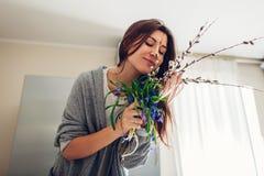 Allergin frigör Lycklig kvinna som luktar buketten av blommor efter återställning på kök Säsongsbetonat allergibegrepp arkivfoto