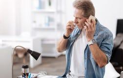 Allergischer Mann, der seinen Handy hält Stockfotos