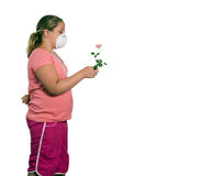 Allergy. A young girl holding a flower while she wears a mask, isolated against a white background Royalty Free Stock Images