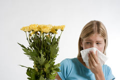 Allergy. Young woman blowing her nose. Flowers representing seasonal allergens Royalty Free Stock Photography