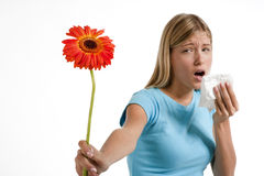 Allergy. Young woman blowing her nose. Flowers representing seasonal allergens Stock Photography