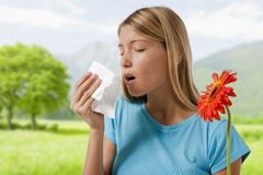 Allergy. Young woman blowing her nose. Flowers representing seasonal allergens Stock Image
