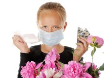 Allergy. Girl standing away from flowers with mask on and pills in hand Royalty Free Stock Photography