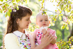 Allergy at blossom. Mother and baby blowing nose outdoors royalty free stock image