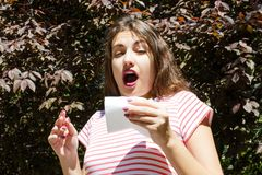 Allergy concept. Sneezing young girl with nose wiper among blooming trees in park.  stock photo