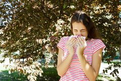 Allergy concept. Sneezing young girl with nose wiper among blooming trees in park.  stock image