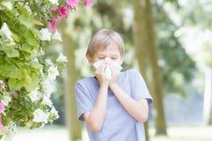 allergy A criança é nariz de sopro com lenço de papel no parque imagens de stock royalty free