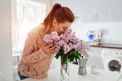 Allergy free. Happy woman smelling lilac in modern kitchen. Seasonal allergy concept. Stock Photos