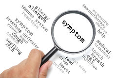 Allergy, health conceptual focus on Symptom. Hand holding magnifying glass focusing on the word Symptom Stock Images