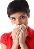Allergy or illness. Close-up of young woman blowing her nose with kleenex on white background (isolated on white Stock Photos