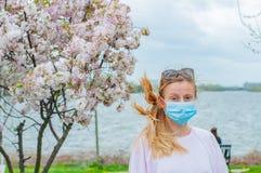 allergy Jovem mulher na máscara protetora da alergia do pólen, entre árvores de florescência no parque imagens de stock