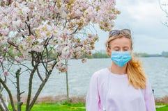 allergy Jovem mulher na m?scara protetora da alergia do p?len, entre ?rvores de floresc?ncia no parque imagem de stock royalty free