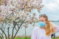allergy Jovem mulher na m?scara protetora da alergia do p?len, entre ?rvores de floresc?ncia no parque fotos de stock
