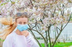 allergy Jovem mulher na m?scara protetora da alergia do p?len, entre ?rvores de floresc?ncia no parque imagem de stock