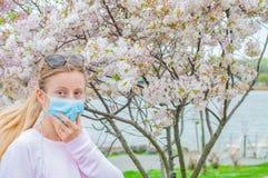 allergy Jovem mulher na m?scara protetora da alergia do p?len, entre ?rvores de floresc?ncia no parque fotografia de stock