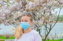 allergy Jovem mulher na m?scara protetora da alergia do p?len, entre ?rvores de floresc?ncia no parque imagens de stock