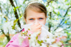 Allergy. Little girl is blowing her nose near spring tree in blo Royalty Free Stock Image