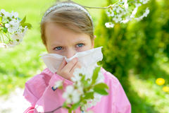 Allergy. Little girl is blowing her nose near spring tree in blo Stock Images