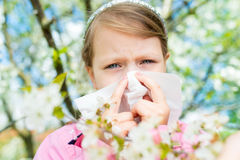 Allergy. Little girl is blowing her nose near spring tree in bloom - sneezing girl. Child with a handkerchief royalty free stock images