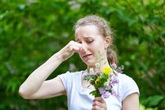 allergy A mulher espremeu seu nariz com m?o, de modo a para n?o espirrar do p?len das flores fotos de stock royalty free