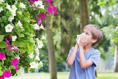 allergy O rapaz pequeno está fundindo seu nariz perto da árvore na flor imagem de stock