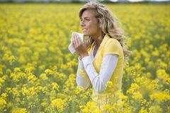 Allergy Season. Young woman sneezing in a flowers meadow. Concept: seasonal allergy Royalty Free Stock Images