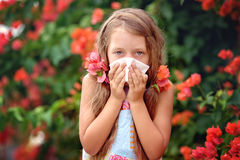Allergy. Spring. Allergy. Little girl is blowing her nose near spring tree in bloom Stock Photo