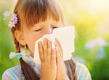 Allergy. Spring portrait of a little girl is blowing her nose Royalty Free Stock Photos