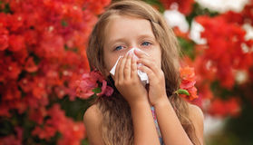 Allergy. Spring portrait. Allergy. Little girl is blowing her nose near spring tree in bloom Stock Images