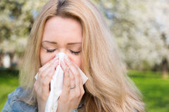 Allergy, Springtime, woman. Woman with allergy sneezing into handkerchief with blooming trees in background stock photography