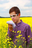 Teenager suffering from pollen allergy. Boy teenager in yellow canola field blowing his nose and suffering from pollen allergy.  Glasses  slightly protect the Stock Photos