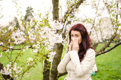 Allergy. A woman sneezing because of pollen allergy in a garden in the spring royalty free stock images