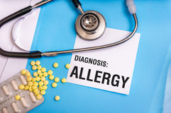 Allergy word written on medical blue folder with patient files. Pills and stethoscope on background royalty free stock photography