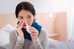 Tired woman with allergy taking useful nasal drops. Allergy. Young woman looking tired of her allergy while taking special nasal drops to cure it Royalty Free Stock Image
