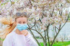 Allergy. Young woman in protective mask from pollen allergy, among blooming trees in park stock image