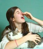 Allergyc a la muchacha adolescente de los gatos que huele con el gato Fotos de archivo libres de regalías