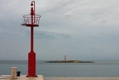 Allerta d'acciaio sul pilastro, sul cielo nuvoloso del fondo e sul lighthou del mare Fotografia Stock