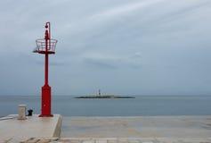 Allerta d'acciaio sul pilastro, sul cielo nuvoloso e sul faro del mare Fotografia Stock Libera da Diritti