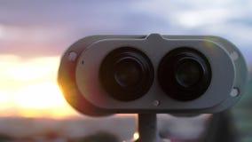 Allerta del binocolo alla città durante il tramonto stupefacente Fotografia Stock