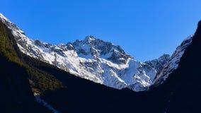 Allerta della valle di Hollyford che offre una vista scenica delle montagne della neve nel parco nazionale di Fiordland Immagini Stock Libere da Diritti