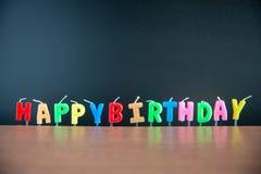 Alles Gute zum Geburtstag des Kerzenständeralphabetwortes mit Tafel auf Bretterboden Stockfotos