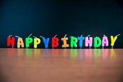 Alles Gute zum Geburtstag des Kerzenständeralphabetwortes mit Tafel auf Bretterboden Lizenzfreie Stockbilder
