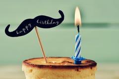 Alles Gute zum Geburtstag des Kuchens, der brennenden Kerze und des Textes Lizenzfreie Stockfotos