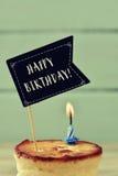 Alles Gute zum Geburtstag des Kuchens, der brennenden Kerze und des Textes Lizenzfreies Stockfoto