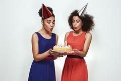 Alles Gute zum Geburtstag! Zwei attraktiv und junge afroe-amerikanisch Frauen in den Parteihüten und in den Abendkleidern brennen lizenzfreie stockbilder