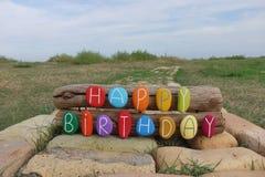 Alles- Gute zum Geburtstagzusammensetzung mit farbigen Steinen auf Holz und Ziegelsteine mit Naturhintergrund lizenzfreie abbildung